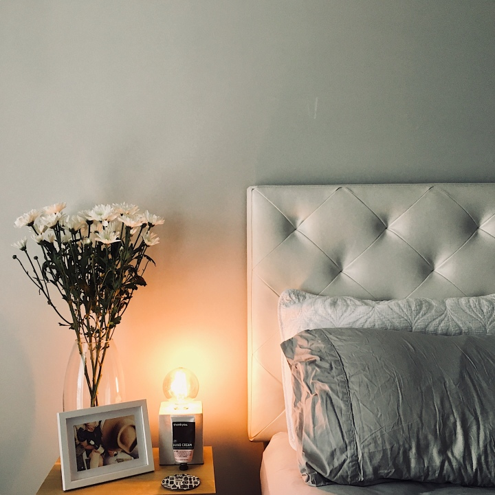 Bedside table with flowers, framed picture, and lamp beside a bed with quilted white bedhead.