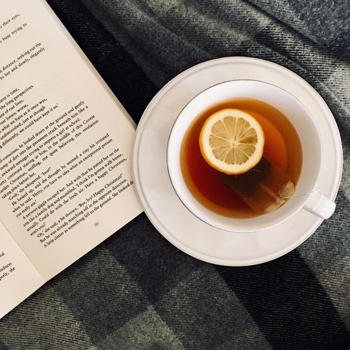 Open book and mug of honey and lemon tea.