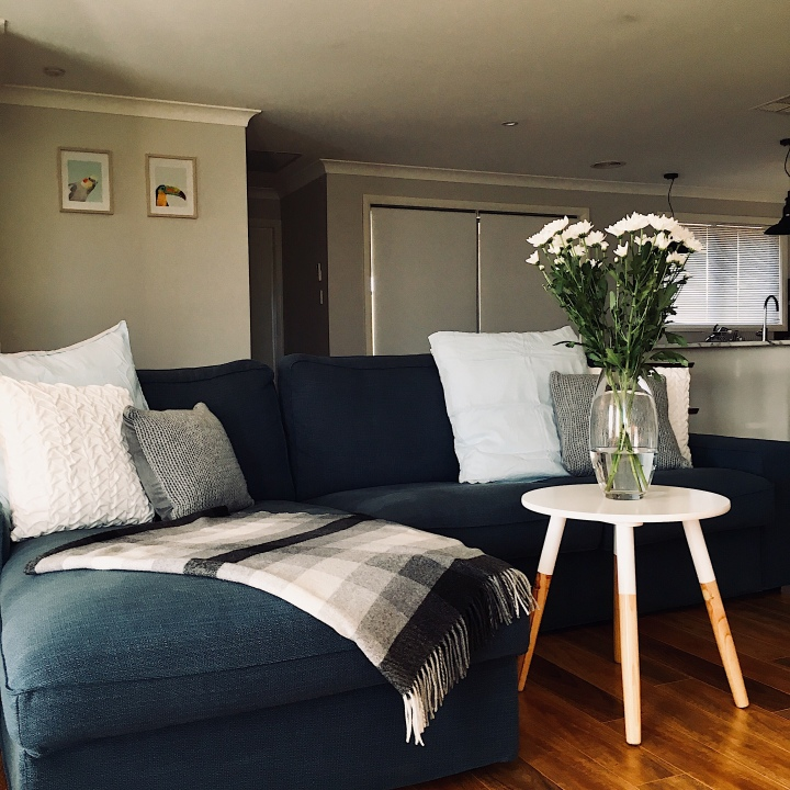 Dark blue lounge, style with blue, grey and white cushions, a black and white throw rug and Scandi inspired lamp table.