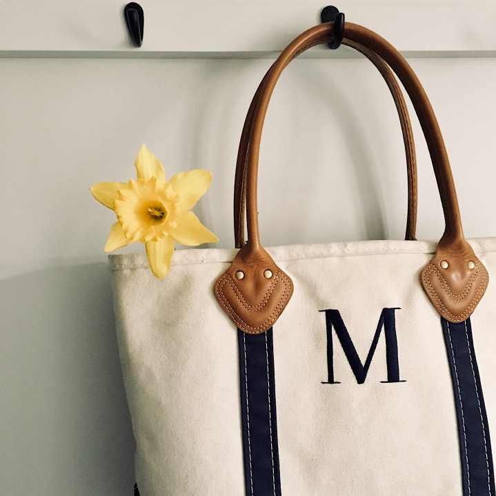 Canvas bag with yellow daffodil sitting inside, hanging on a coat rack.
