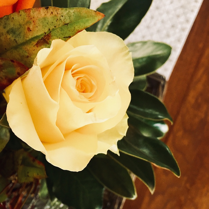 Looking down on a yellow rose in a bunch of flowers.
