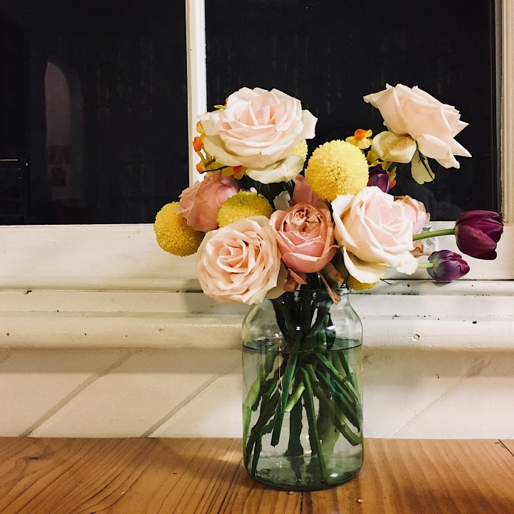 A bunch of flowers sitting on a table by a window.