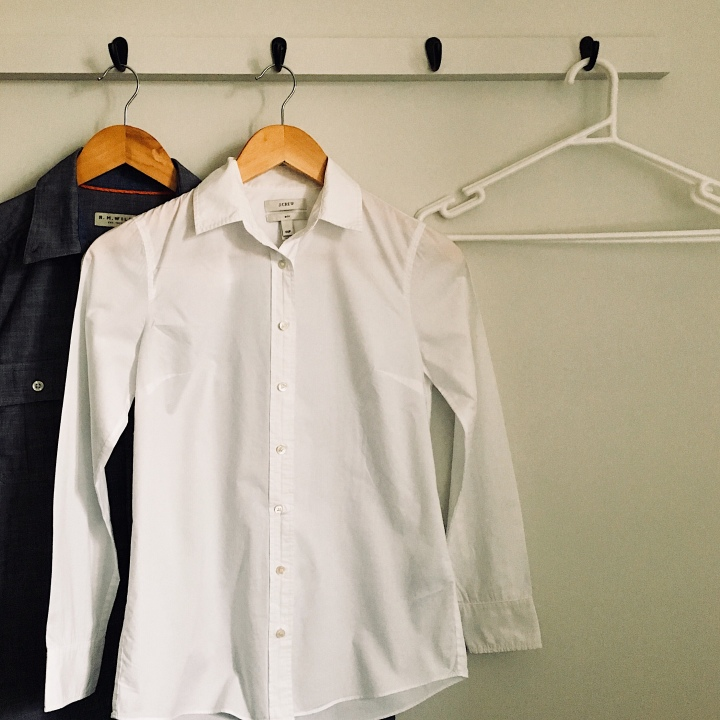 Shirts and coat hangers on a coat rack.