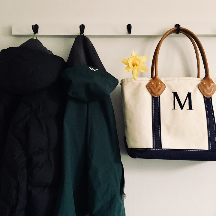 Coats and a canvas bag hanging on a coat rack.