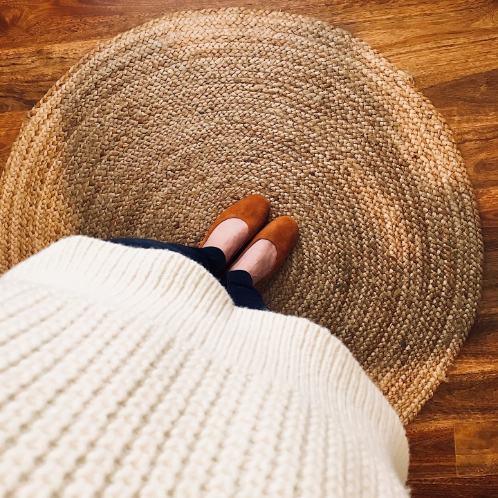 Woman standing on jute rug wearing Everlane Day Heel in cognac suede and Everlane Wool-Cashmere Waffle Square Crew in cream.