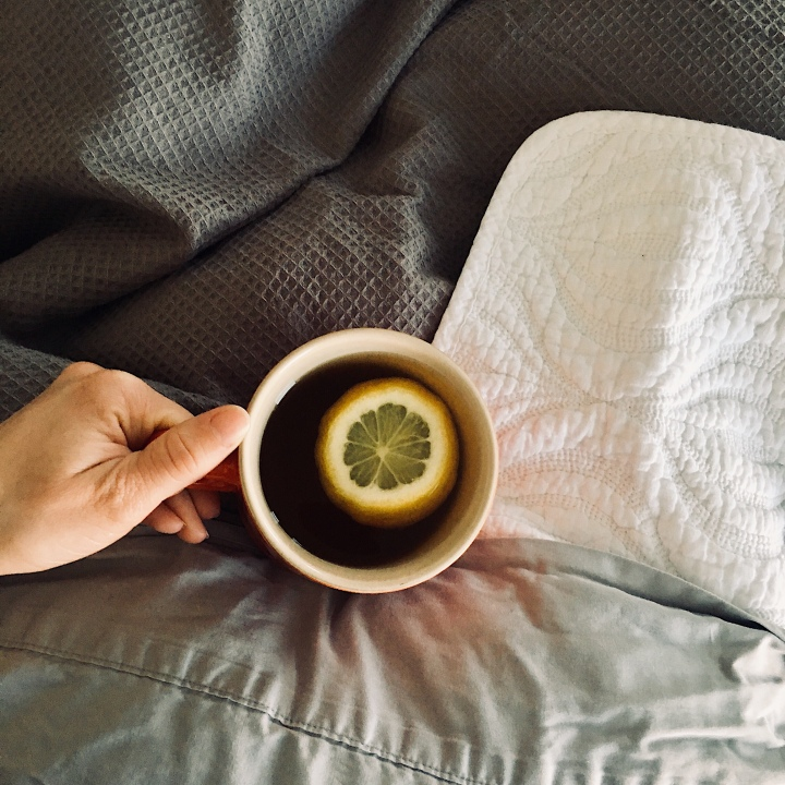 Woman in bed drinking a cup of tea with a slice of lemon.