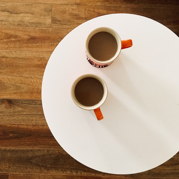 Two coffee cups sitting on a round white table.