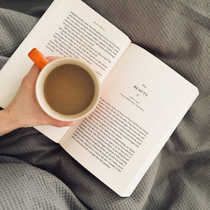 Woman holding a mug of coffee, reading a book in bed.