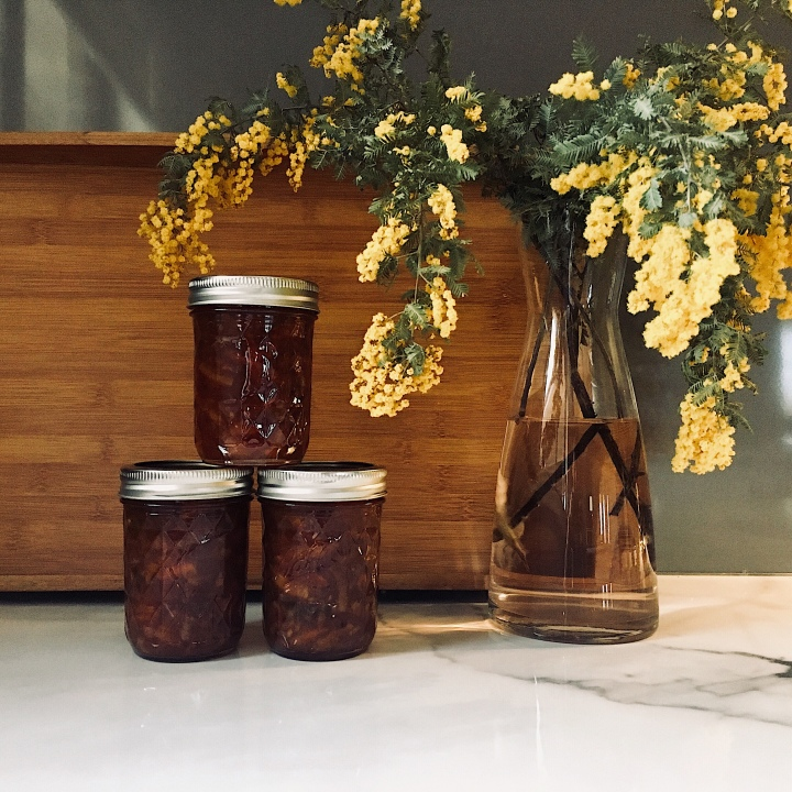 Jars of marmalade beside a vase of Australian wattle.