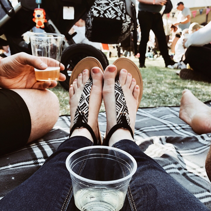 Feet on a picnic blanket at the Gears and Beers festival in Wagga Wagga, New South Wales, Australia.