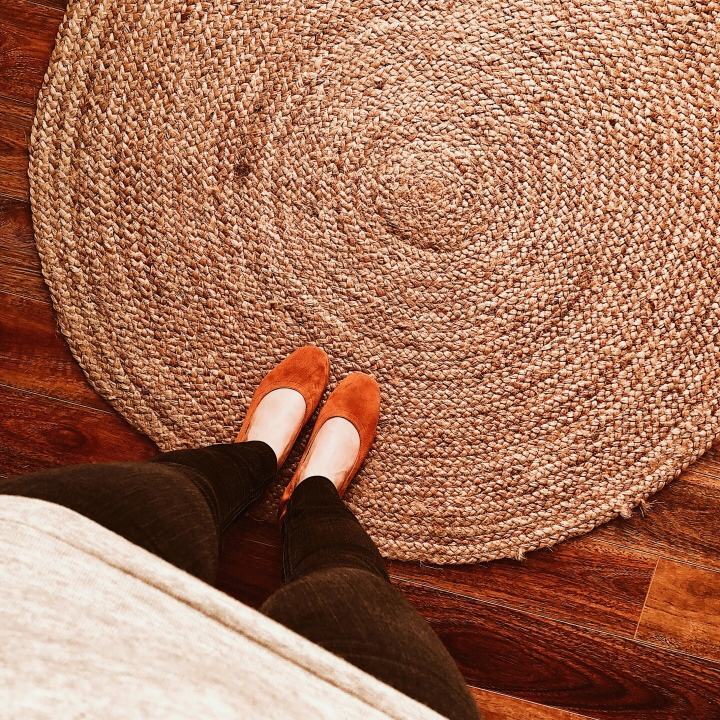 Woman standing in cognac Everlane day heels on jute rug.