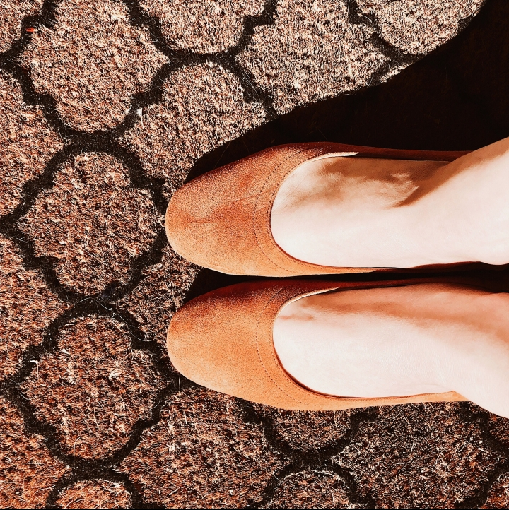 Woman standing in cognac Everlane day heels on patterned door mat.