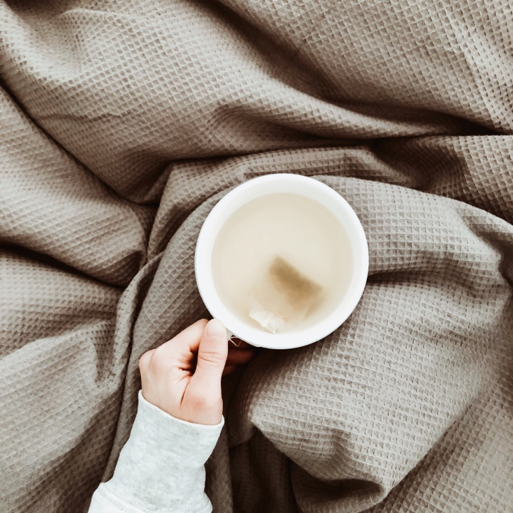 Woman holding a cup of tea of a grey duvet.