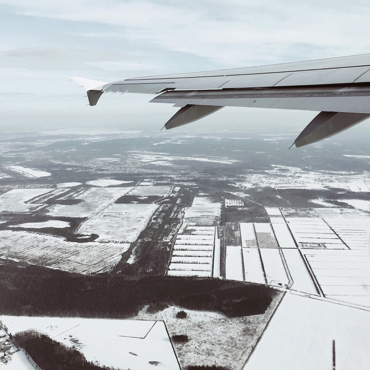 Looking out of a plane window onto a snowy landscape.