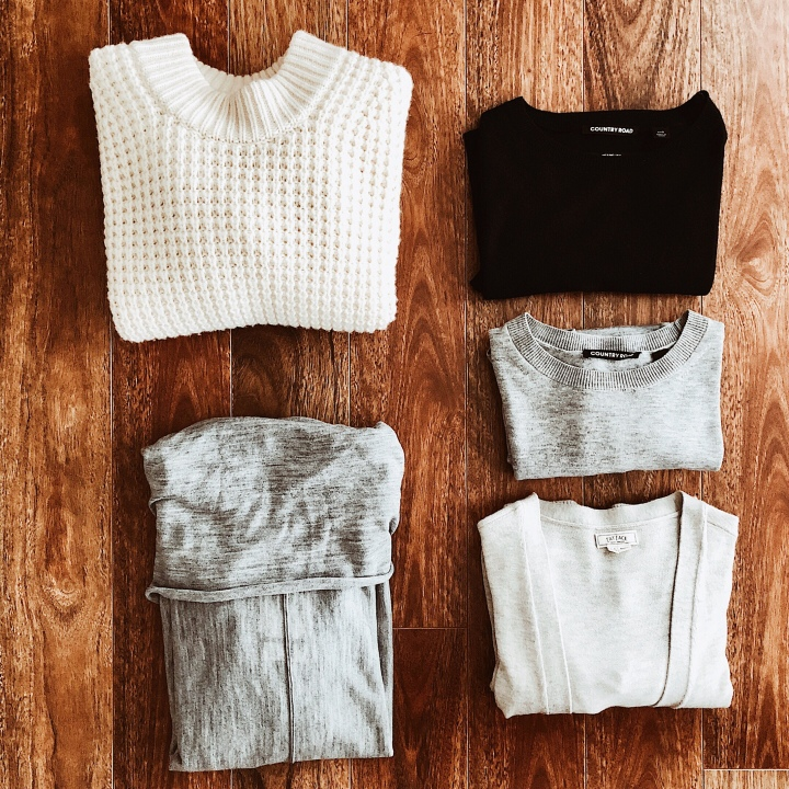 Flat lay of knitwear in cream, navy and grey
