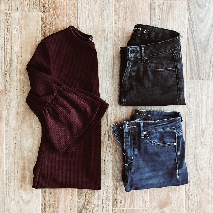 Flat lay of burgundy frill sleeve dress, dark blue jeans, black jeans.