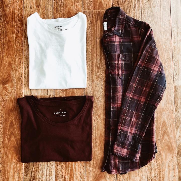Flat lay of burgundy and blue check shirt, white t-shirt, burgundy t-shirt