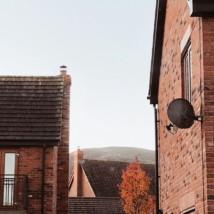 Looking towards the Malvern Hills in Worcestershire England, through brown brick buildings.