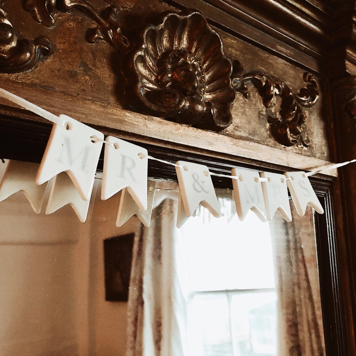 Ceramic bunting hanging above a mirror, spelling out Mr and Mrs.