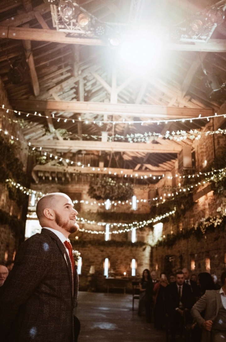 Groom awaiting bride in a fairy light lit stone barn.
