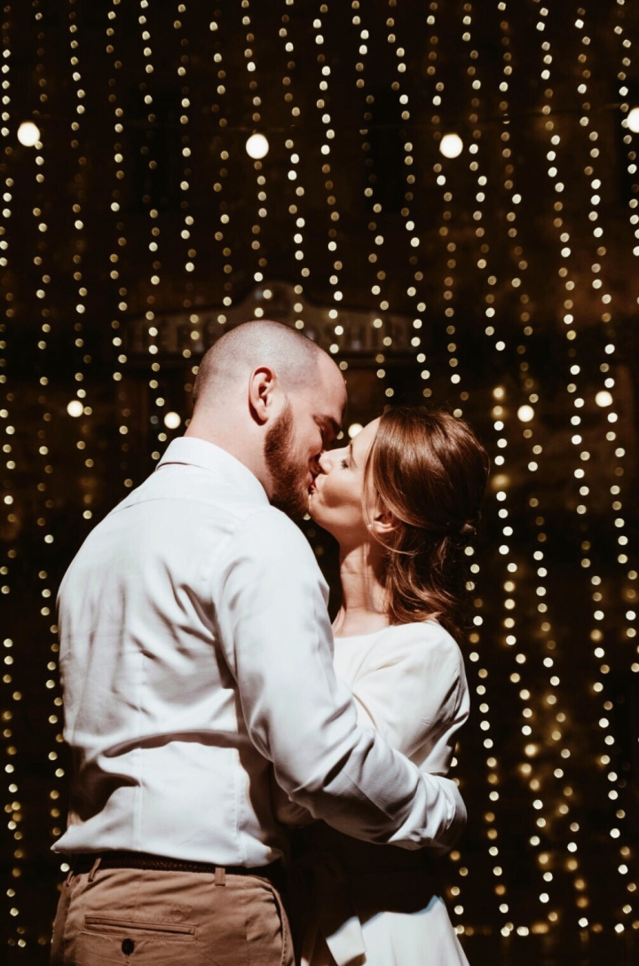 Bride and groom kissing in front of strings of fairy lights.