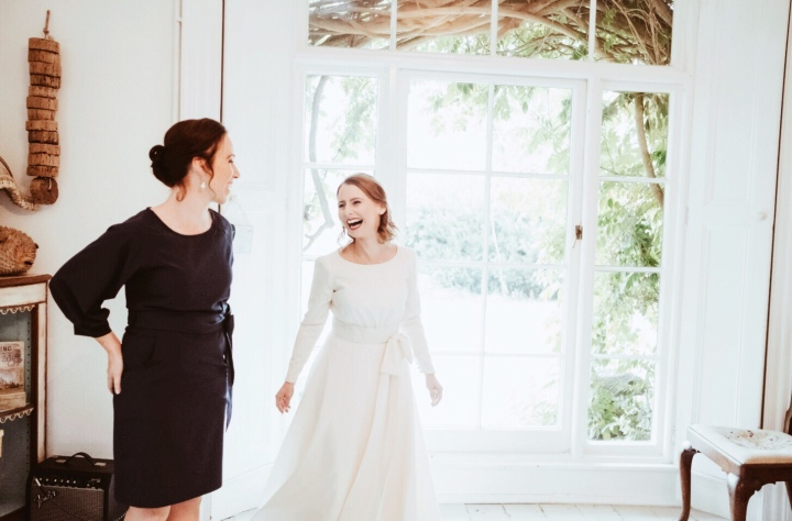 Bride and bridesmaid laughing in front of a window.