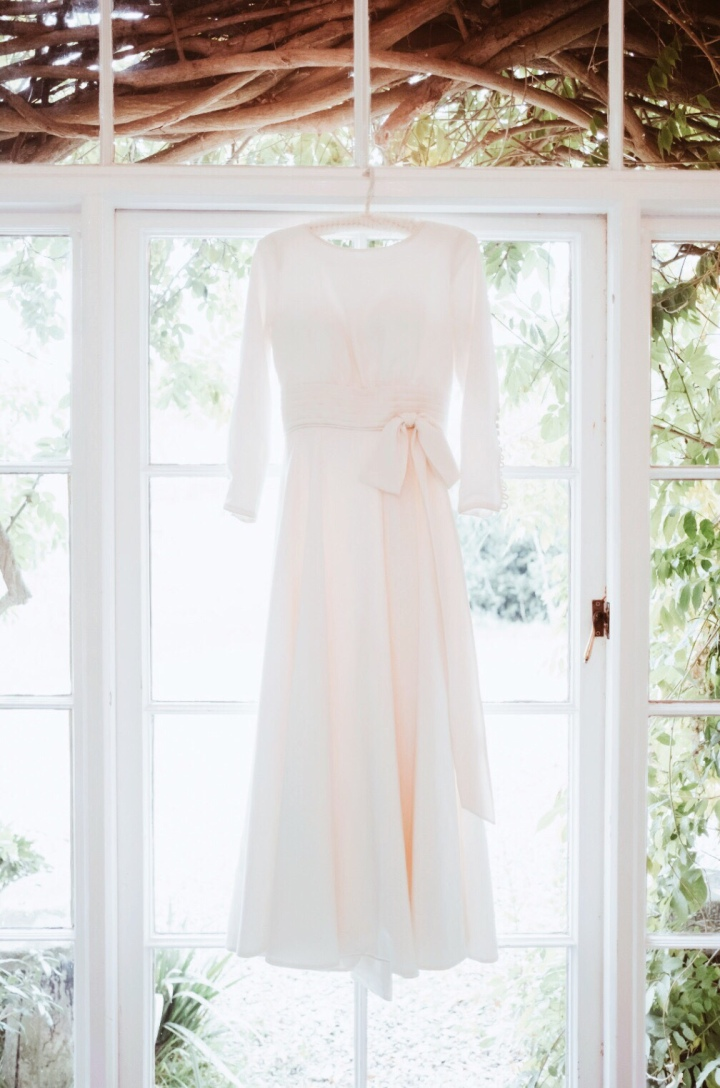 Long sleeved wedding dress hanging in a window surrounded by vines.