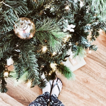 Feet in flip flops standing under a Christmas tree.