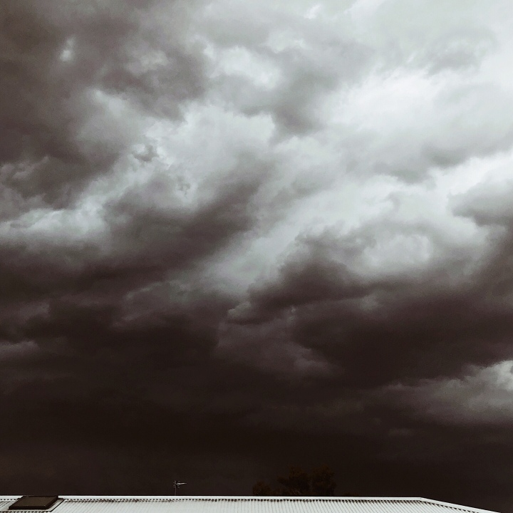 Dark storm clouds hover over a white tin roof in Australia.