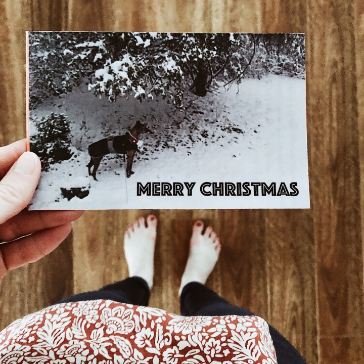 Barefoot woman holding a Christmas card featuring a dog standing in the snow.