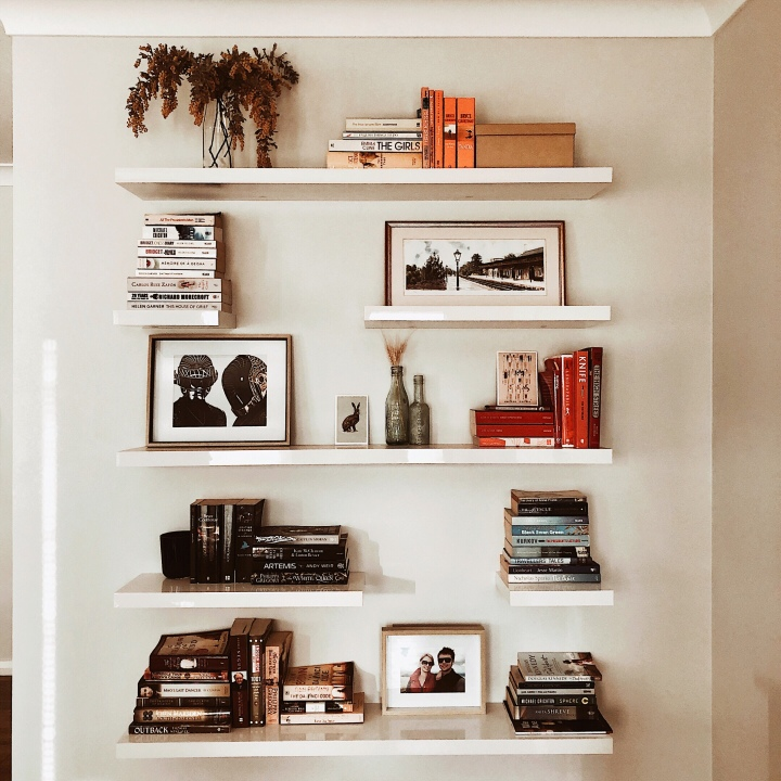 Bookshelves filled with flowers, artwork, postcards, photos and knick knacks.