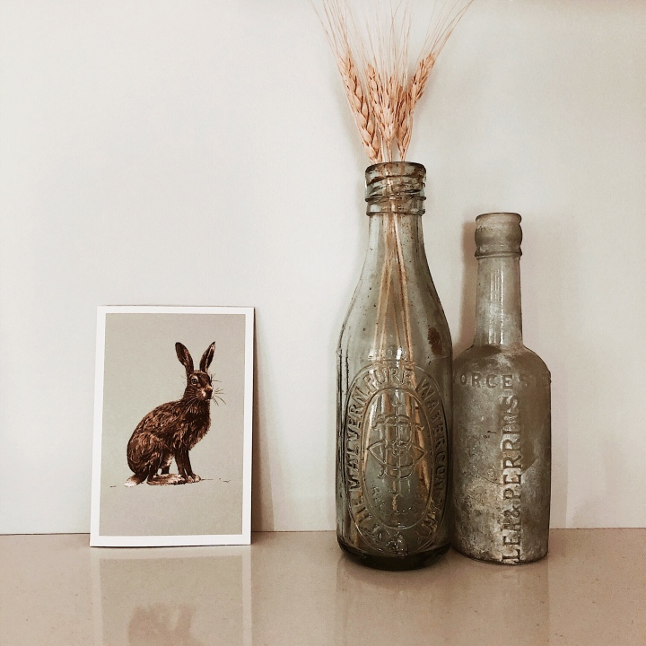 Card with picture of a hare sitting beside two old bottles.