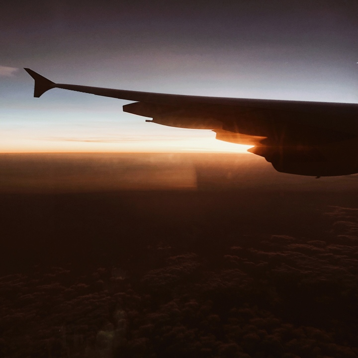 The silhouette of a plane wing against the sunset.