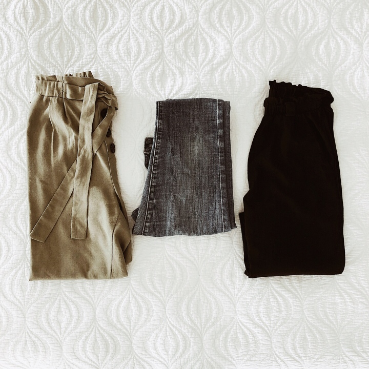 Flat lay of khaki trousers, denim jeans and black linen trousers.