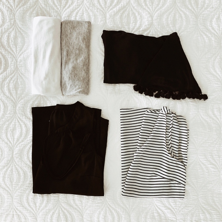Flat lay of black, white, grey and navy tops.