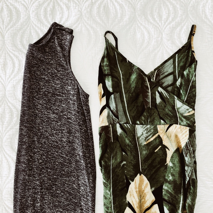 Flat lay of navy t-shirt dress and green and black summer dress.