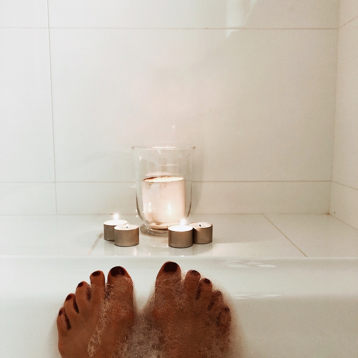 Feet in a bubble bath, looking onto a collection of candles.