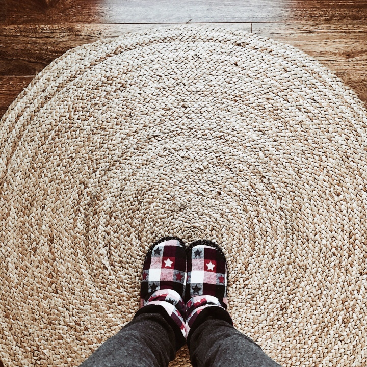 Looking down at a woman wearing slippers on a jute rug.