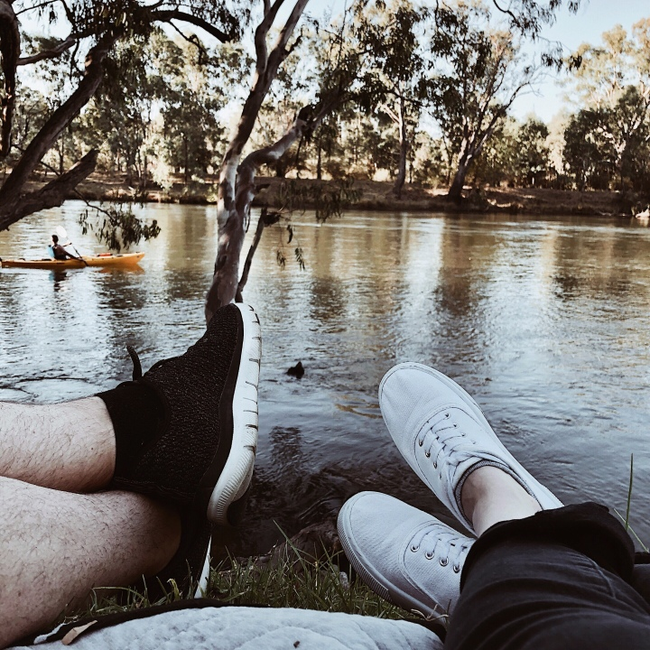 Two sets of feet on the banks of the Murray River at Albury, New South Wales, Australia.