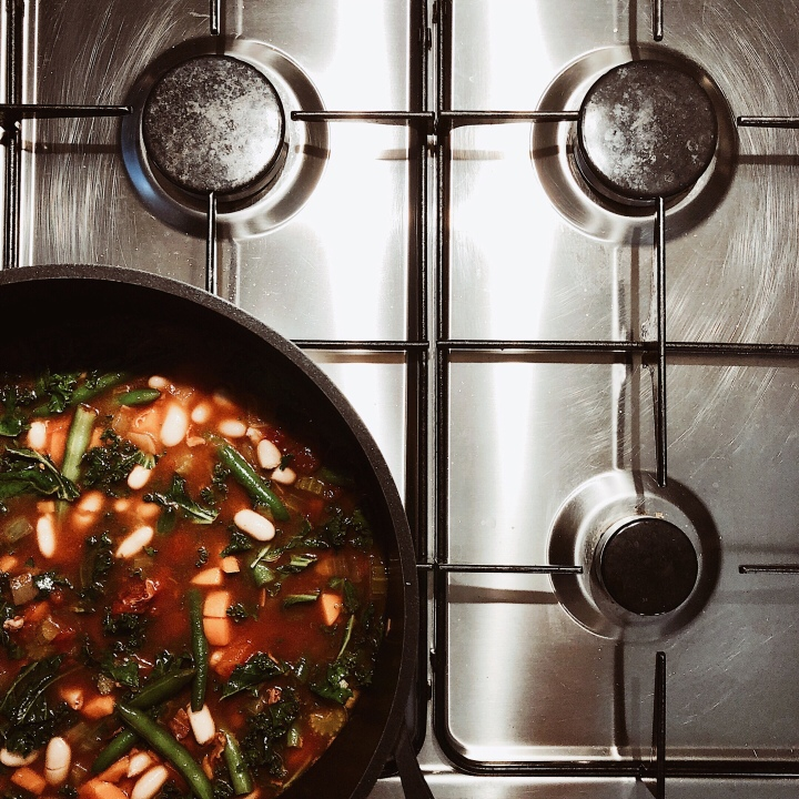 A pot of ribollita or Tuscan bread soup on a gas stove.