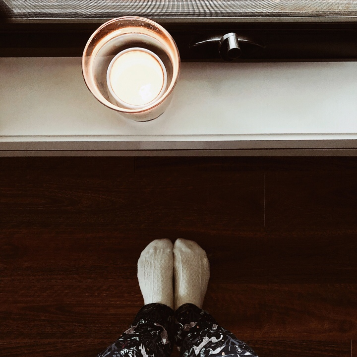 Looking down at a pair of feet in white cashmere socks and a candle sitting on a window-sill.