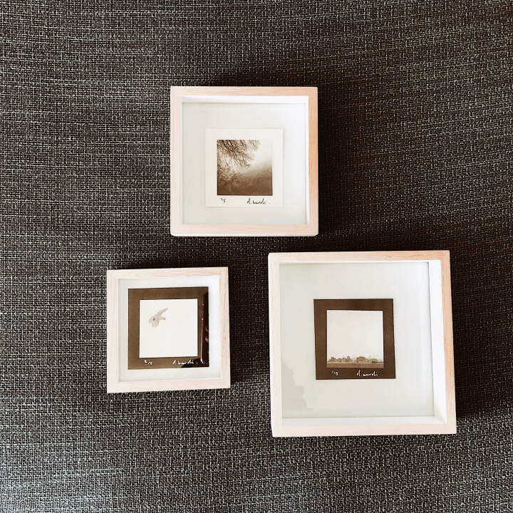 Three framed black and white photographs.