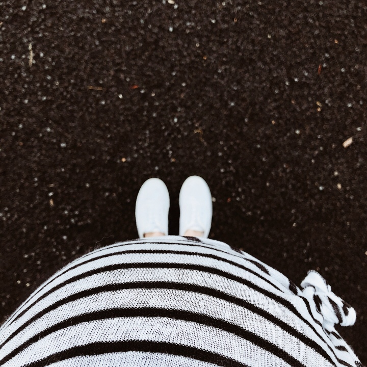 Pregnant woman in black and white stripe shirt looking at white sneaker clad feet.