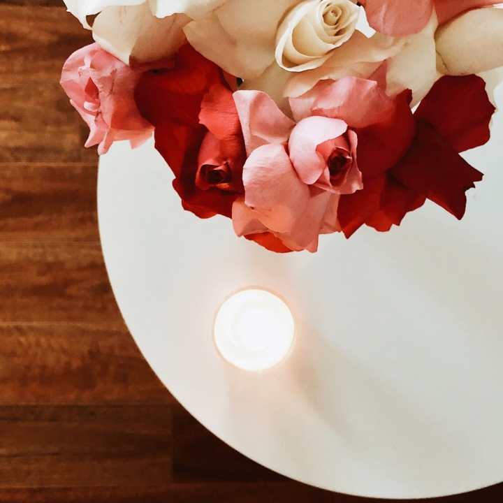 A bunch of roses sitting on a white table beside a lighted candle.