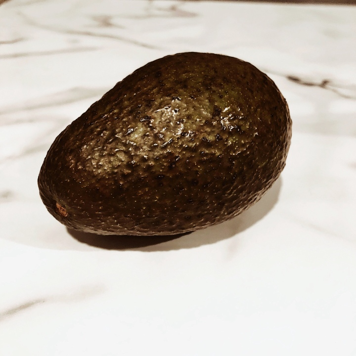 Hass avocado sitting on a black and white marbled surface.