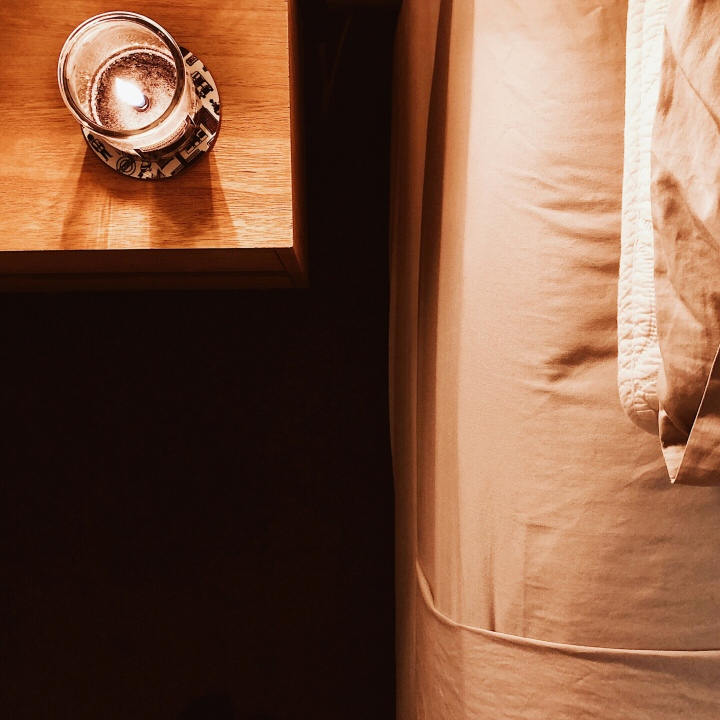 Candle on beside table, beside bed.