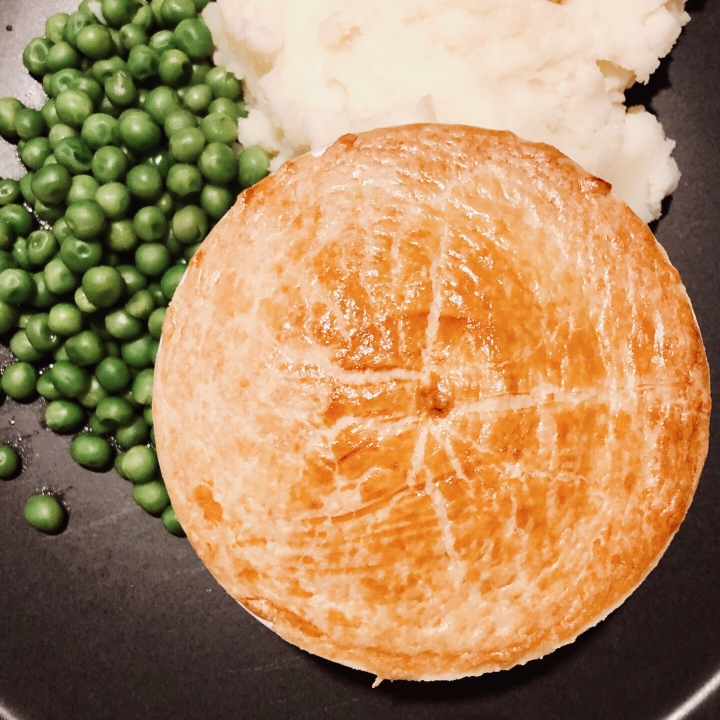 Pastry lid of a pot pie with mashed potato and peas.