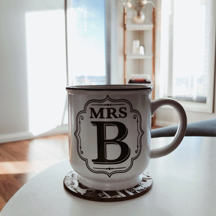 A mug of tea sitting on a table in a bright lounge room.