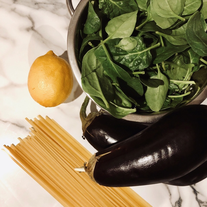 Spinach leaves, aubergines, pasta and a lemon on a marbled kitchen surface.