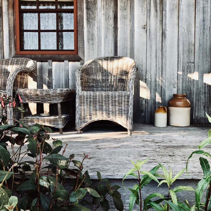 Wicker chairs sitting on the verandah of Settlers Cottage in Kangaroo Valley, New South Wales, Australia.